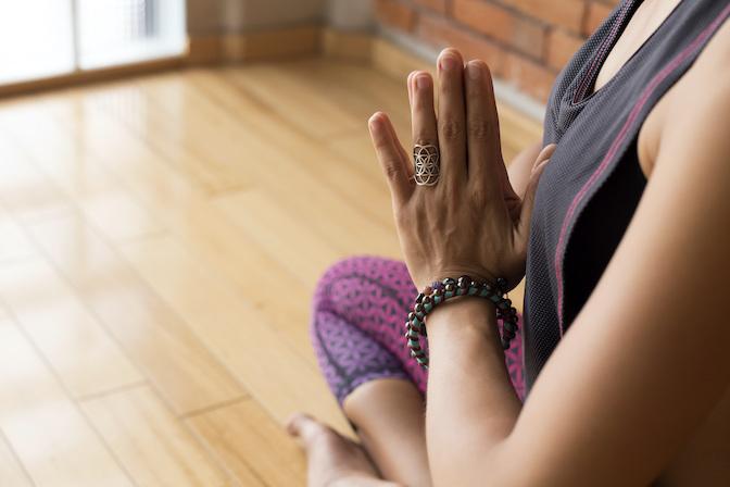 Namasté kennen die meisten aus dem Yoga - Frau in der Yogastunde zeigt das Namaste Zeichen
