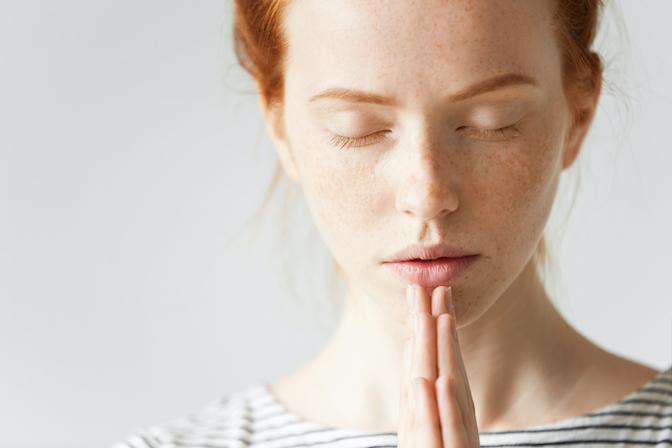 Namaste - junge europäische Frau hat die Augen geschlossen und hält ihre Hände vor der Brust zusammen