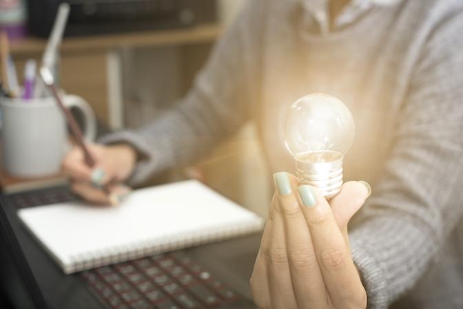 Visualisieren lernen - Frau sitzt am Schreibtisch und trägt eine Glühbirne