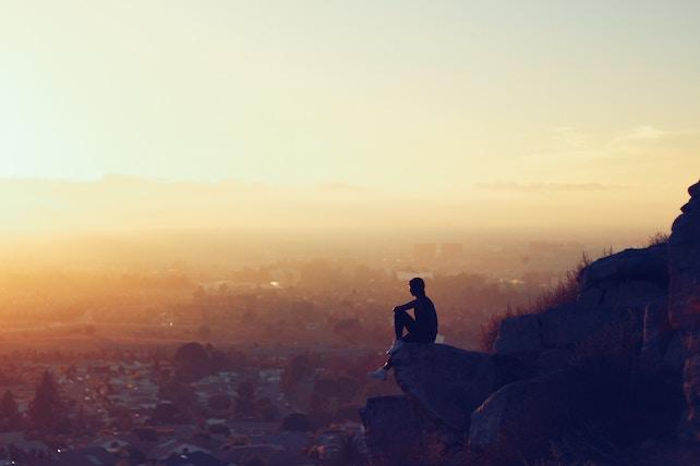 Mann sitzt beim Sonnenuntergang auf einer Klippe und ist nachdenklich - innere Ruhe innerer Frieden
