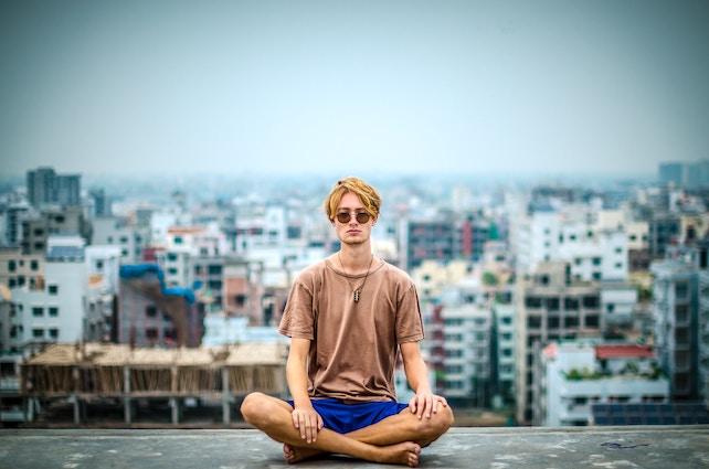 junger Mann meditiert auf dem Dach eines Hauses- innere Leere
