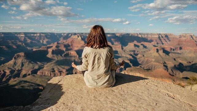 junge Frau meditiert auf einem Berg - der Weg zurErleuchtung